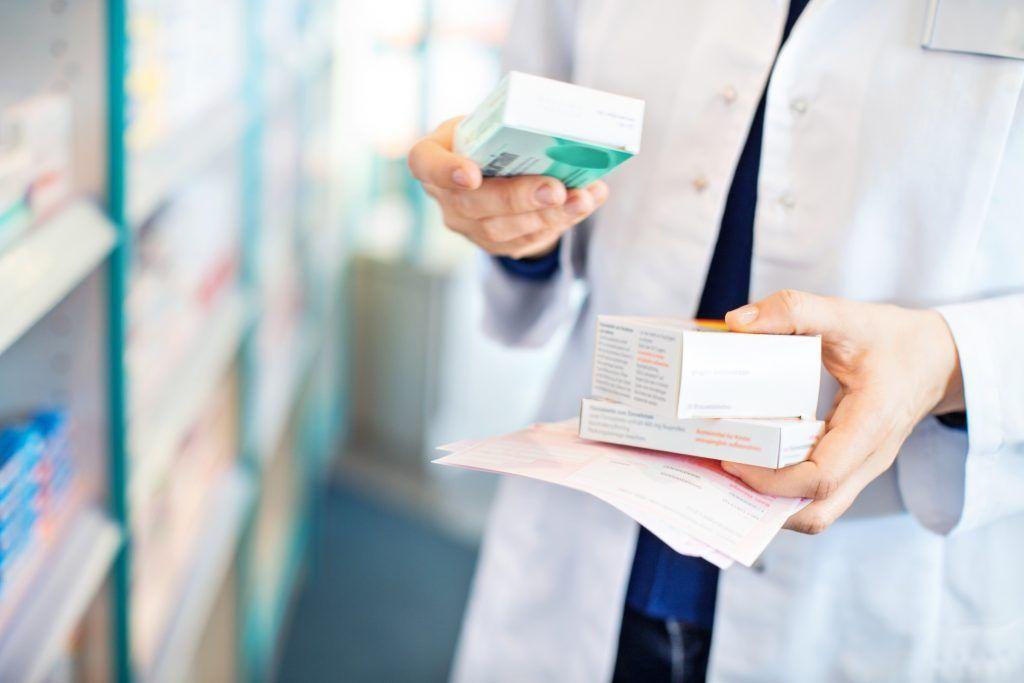 Farmasøyt som holder noen esker med medisiner på apotek.