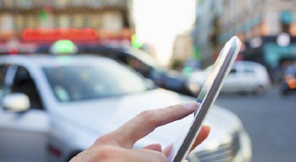 Bilde av hånd som trykker på mobil med drosje i bakgrunnen.