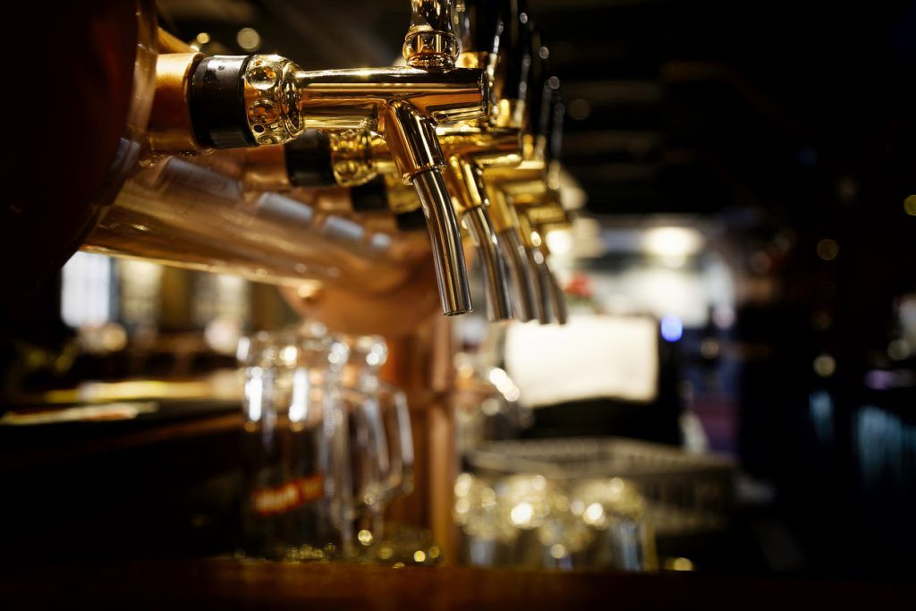Foto av flere ølkraner i en bar.