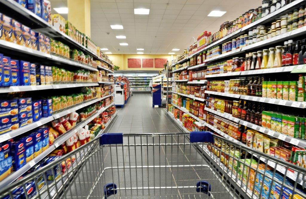 Foto av handlevogn mellom reoler i dagligvarebutikk.