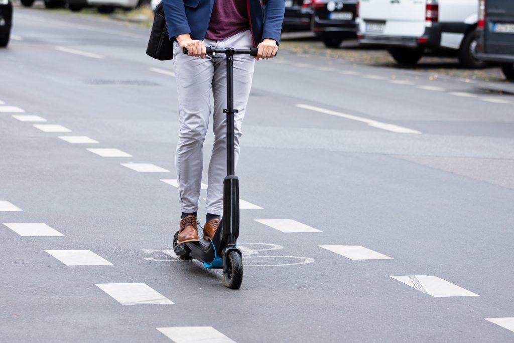 Mann som kjører elsparkesykkel